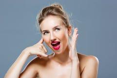 Het meisje met het heldere make-up tonen roept me gebaar over grijze achtergrond Stock Afbeeldingen