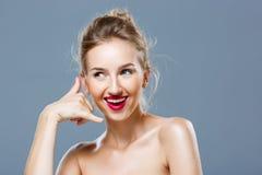 Het meisje met het heldere make-up tonen roept me gebaar over grijze achtergrond Royalty-vrije Stock Afbeeldingen