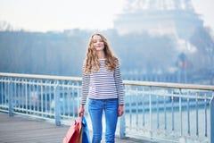 Het meisje met het winkelen doet dichtbij de toren van Eiffel in zakken stock foto