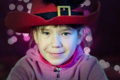 Het meisje met hoed kijkt met de lichten van Kerstmis Royalty-vrije Stock Afbeeldingen