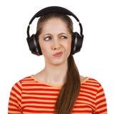 Het meisje met hoofdtelefoons drukt negatieve emoties uit Stock Afbeeldingen