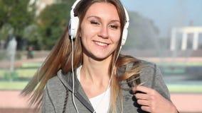 Het meisje met hoofdtelefoons spint synchroon met de camera stock video