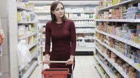 Het meisje met karretje gaat onder planken met goederen in kruidenierswinkelopslag, steadicam schot stock footage