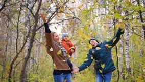 Het meisje met kinderen in de herfstpark werpt gele bladeren Lachende en glimlachende gelukkige familie stock videobeelden
