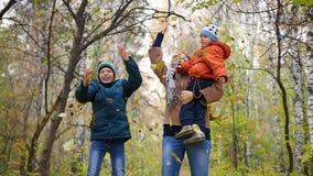 Het meisje met kinderen in de herfstpark werpt gele bladeren Lachende en glimlachende gelukkige familie stock video