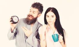 Het meisje met koffiekop, mens houdt klok in hand Het paar, familie ontwaakte op tijd Paar in liefde, jonge familie in pyjama royalty-vrije stock fotografie