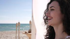 Het meisje met krullen, gebaar hello en glimlach, drinkt cocktail Ñ  oconut, exoticism, zomer, op achtergrond overzeese oceaan stock video