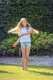 Het meisje met lang blond haar danst in de tuin op een mooie de lentedag en is vrolijk royalty-vrije stock foto's