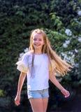 Het meisje met lang blond haar danst in de tuin op een mooie de lentedag en is vrolijk stock fotografie