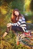 Het meisje met lang bruin los haar zit op fiets stock afbeeldingen