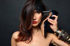 Het meisje met lang haar, de rode lippen en de juwelen van armbanden van zwarte high-heeled schoenen zetten de hiel aan zijn temp stock fotografie