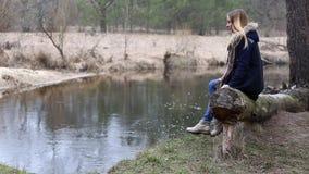 Het meisje met lang haar, die bij het water op de rivierbank zitten stock video