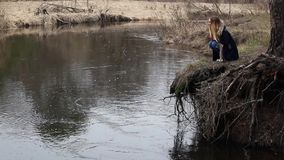 Het meisje met lang haar, die door het water op de rivierbank zitten stock video