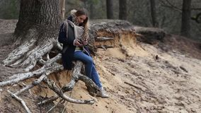 Het meisje met lang haar, die in het water op de rivierbank zitten stock footage