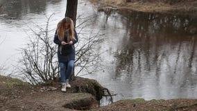 Het meisje met lang haar, die in het water op de rivierbank zitten stock videobeelden