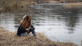 Het meisje met lang haar, die in het water op de rivierbank zitten stock video