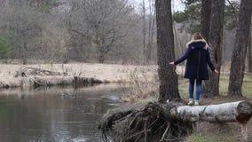 Het meisje met lang haar, die langs het water op de rivierbank lopen stock videobeelden