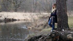 Het meisje met lang haar, door het water op de rivierbank stock footage