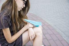 Het meisje met lang haar houdt een document vliegtuig op haar knieën met de woordtoekomst Concept carrièrekeus Royalty-vrije Stock Fotografie