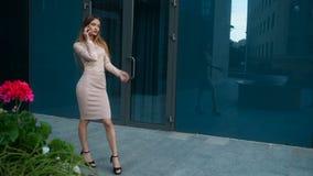 Het meisje met lang haar op de hielen en de in kledij bevindt op de straat en zich gezegd door mobiele telefoon stock footage