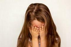 Het meisje met lang haar verborg haar gezicht met haar handen uitdrukkend wrok royalty-vrije stock foto's