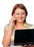 Het meisje met laptop spreekt door een mobiele telefoon royalty-vrije stock foto