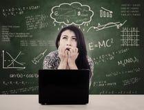Het meisje met laptop is zenuwachtig onder ogen ziend examen Stock Foto's