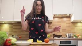Het meisje met mooi lang zwart haar in pyjama's kookt thuis Zij zingt en danst in een zeer goede stemming stock video