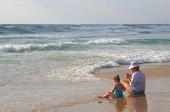 Het meisje met mum zit op kust. royalty-vrije stock afbeeldingen