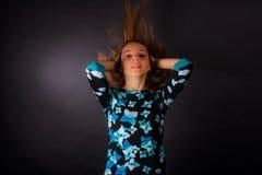 Het meisje met het ontwikkelen van lang haar op zwarte achtergrond stock foto