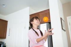 Het meisje met oranje fruit heeft pret in keuken stock afbeelding
