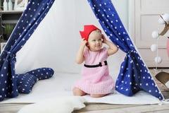 Het meisje met rode koronjq zit in een wigwam Stock Foto