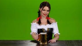 Het meisje met rode lippen en een Beiers kostuum dient bier Het groene scherm stock footage