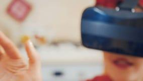 Het meisje met rode lippen gebruikt virtuele werkelijkheidsglazen stock footage