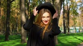 Het meisje met rode lippen zet op modieuze hoed stock video
