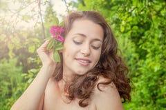 Het meisje met rode roze bloem in haar dient park in Stock Afbeelding