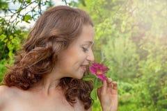 Het meisje met rode roze bloem in haar dient park in Royalty-vrije Stock Afbeelding