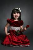 Het meisje met rode satijnkleding en nam toe Royalty-vrije Stock Foto's