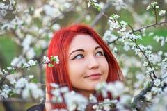 Het meisje met rood haar inhaleert de geur van de bloemen van de boom royalty-vrije stock foto