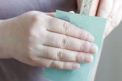 het meisje met schuurpapier poetst spaanplaat, triplex op Close-up stock foto's