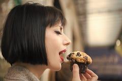 Het meisje met sensueel gezicht eet bosbessenmuffin in Parijs, Frankrijk royalty-vrije stock afbeeldingen