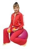Het meisje met sinaasappelen op fitbol Stock Fotografie