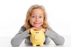 Het meisje met spaarvarken is gelukkig en glimlachend Royalty-vrije Stock Foto's