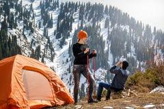 Het meisje met spoorstokken en een kerel met verrekijkers op een halt dichtbij een toeristentent in de bergen onderzoeken de omge stock foto's