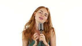 Het meisje met sproeten zingt in een retro microfoon Witte achtergrond stock footage