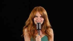 Het meisje met sproeten zingt in een retro microfoon Zwarte achtergrond stock videobeelden