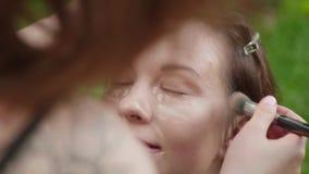 Het meisje met stichting en poetsmiddel op gezicht bekijkt camera en maakt omhoog kunstenaar mengt alles voordien met borstel stock footage