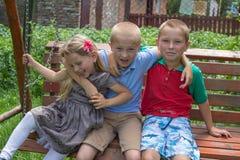 Het meisje met twee broers, het ontmoeten van klasgenoten` kinderen op de bank omhelst stock fotografie