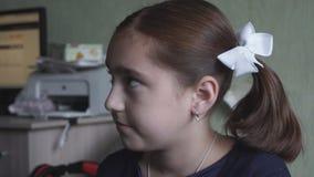Het meisje met vlechten wrijft haar ogen stock footage