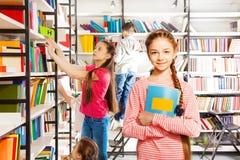 Het meisje met vlechttribunes, houdt notitieboekje in bibliotheek Stock Foto